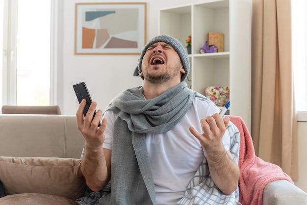 Verärgerter kranker mann mit schal um den hals mit wintermütze, der thermometer und telefon hält, sitzt auf der couch im wohnzimmer
