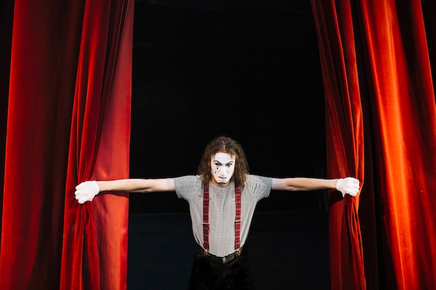 Verärgerter männlicher pantomimekünstler, der roten vorhang hält