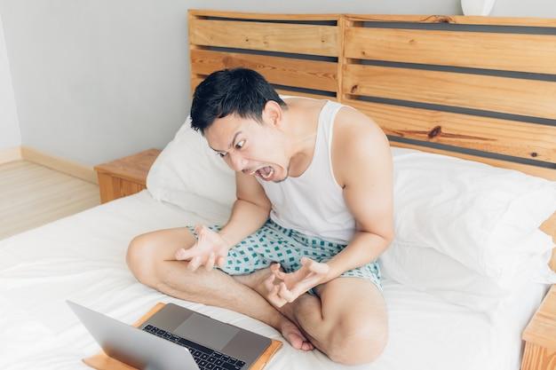 Verärgerter mann arbeitet mit seinem laptop auf seinem bett. konzept der freiberuflerprobleme.
