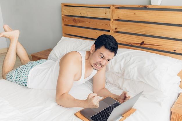 Verärgerter mann arbeitet mit seinem laptop auf seinem bett.