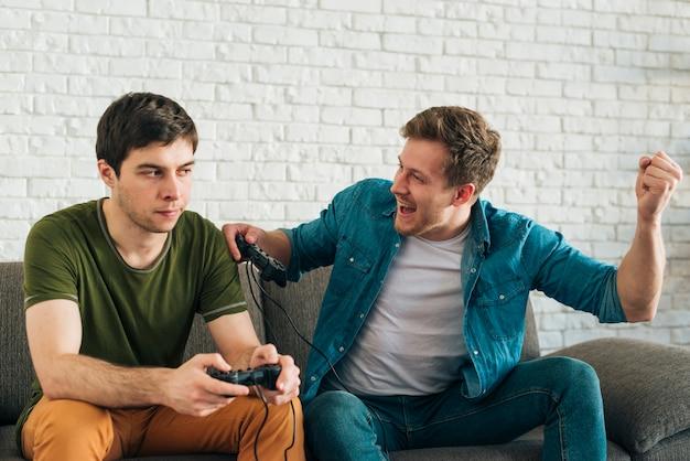 Verärgerter mann, der den mann zujubelt betrachtet, nachdem das videospiel gewonnen worden ist