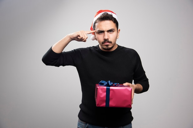 Verärgerter mann, der eine geschenkbox über einer grauen wand hält.