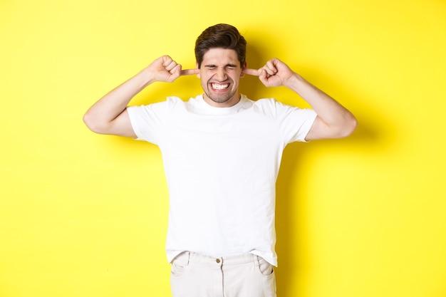Verärgerter mann, der eine grimasse verzieht und die ohren schließt, sich über laute geräusche beschwert und vor gelbem hintergrund steht