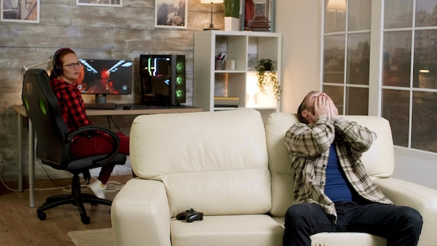 Verärgerter mann, der einen drahtlosen controller auf die couch wirft, nachdem er nach dem spielen von videospielen verloren hat. freundin im hintergrund.