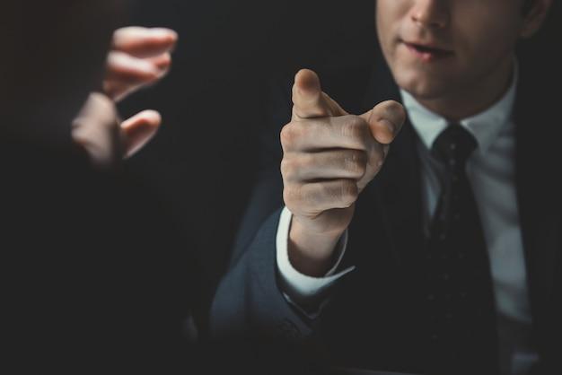 Verärgerter mann, der hand auf jemand zeigt, mit dem er spricht