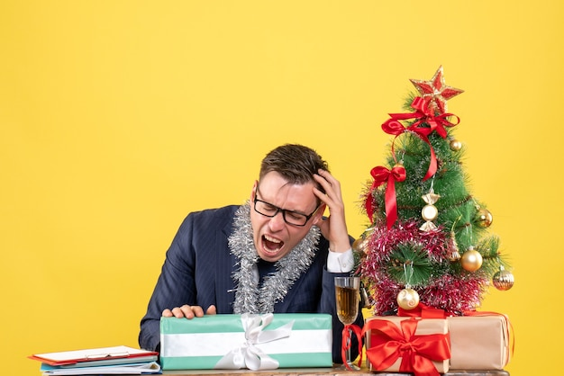 Verärgerter mann der vorderansicht, der am tisch nahe weihnachtsbaum sitzt und auf gelbem hintergrund präsentiert