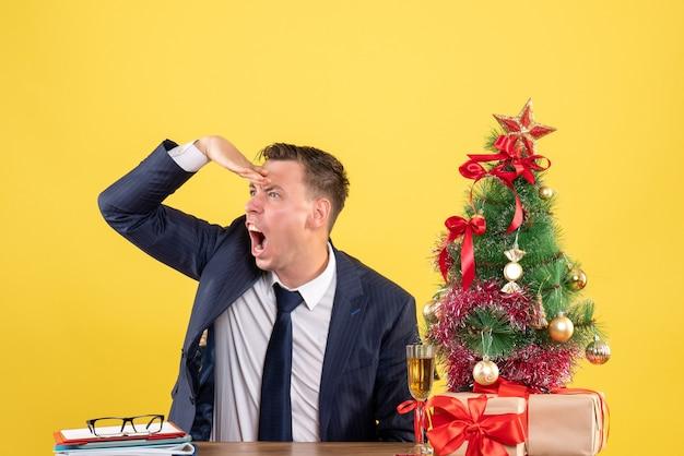 Verärgerter mann der vorderansicht, der das sitzen am tisch nahe weihnachtsbaum und geschenken auf gelbem hintergrund beobachtet