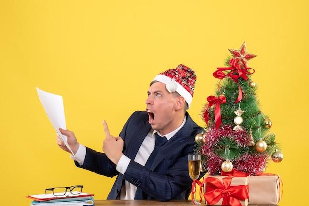 Verärgerter mann der vorderansicht, der papiere zeigt, die am tisch nahe weihnachtsbaum sitzen und auf gelbem hintergrund präsentieren