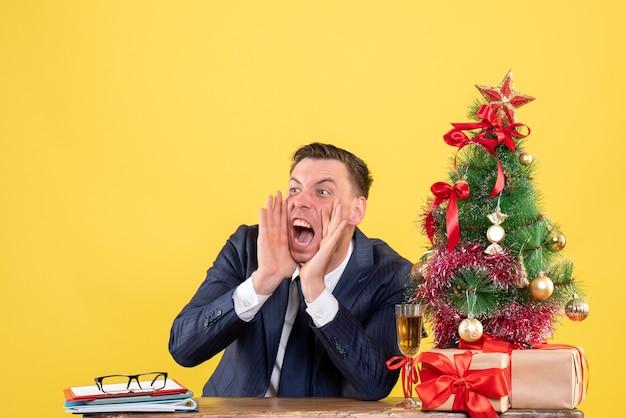 Verärgerter mann der vorderansicht, der schreit, während er am tisch nahe weihnachtsbaum sitzt und auf gelbem hintergrund präsentiert