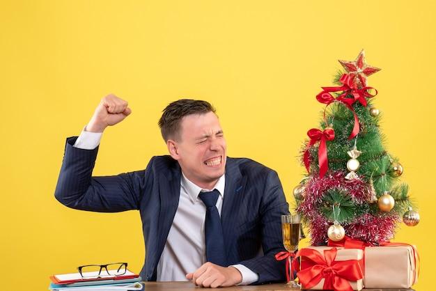 Verärgerter mann der vorderansicht, der seine hand erhöht, die am tisch nahe dem weihnachtsbaum und den geschenken auf gelbem hintergrund sitzt