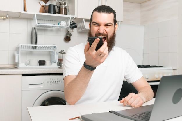 Verärgerter mann, der zu hause in der küche arbeitet und smartphone schreit