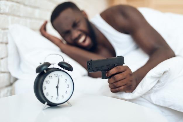 Verärgerter mann des afroamerikaners, der auf den wecker mit der gewehr zeigt. morgen