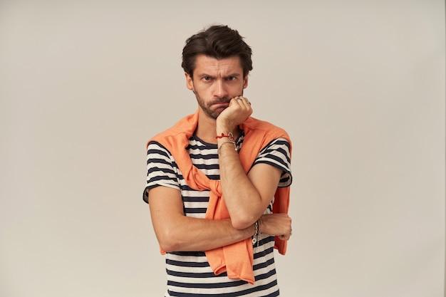 Verärgerter mann mit brünetten haaren und borsten. tragen eines gestreiften t-shirts und eines orangefarbenen pullovers auf den schultern. lehnen sie sein kinn an die hand