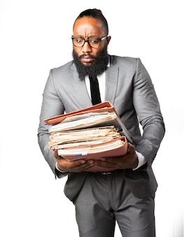Verärgerter mann mit vielen papieren und ordnern