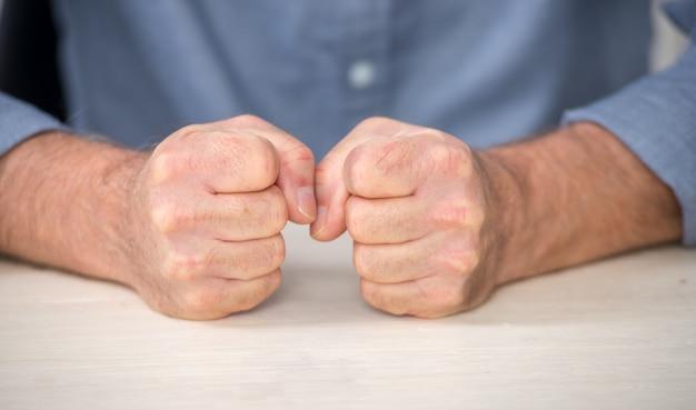 Verärgerter mann, nahaufnahme seiner fäuste