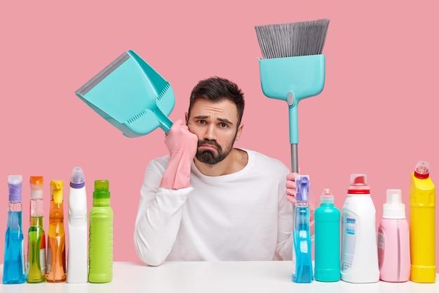 Verärgerter müder ehemann trägt rosa gummihandschuhe, trägt besen und schaufel, macht pause, nachdem er den boden gekehrt hat, putzt das haus mit einem reinigungsmittel
