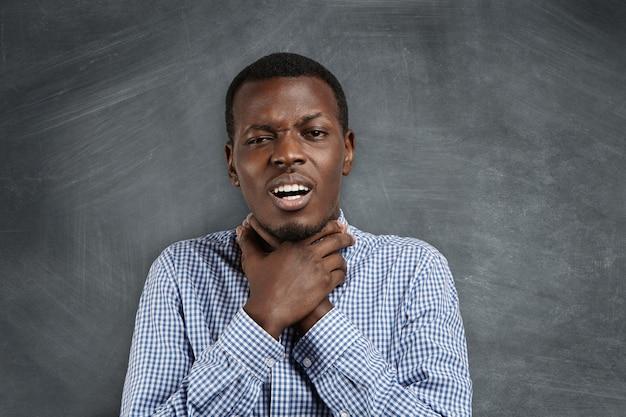 Verärgerter mürrischer junger afrikanischer lehrer oder schüler in freizeithemd, der sich am hals hält und selbstmordgeste macht, als würde er versuchen, sich zu ertrinken oder zu würgen, und seine gereizte und satt gewordene haltung zeigt