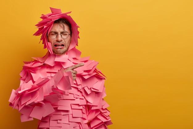 Verärgerter niedergeschlagener mann weint verzweifelt, zeigt auf eine leere stelle, unzufrieden mit verkaufsrabatten, viele rosa aufkleber kleben über dem körper, isoliert an der gelben wand. unglückliche verzweifelte gefühle