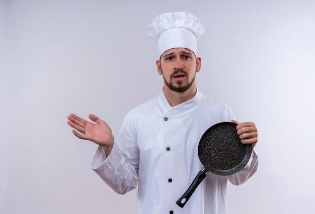 Verärgerter professioneller männlicher koch kocht in der weißen uniform und im kochhut, der eine pfanne hält, die verwirrt steht über weißem hintergrund steht