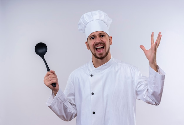 Verärgerter professioneller männlicher kochkoch in der weißen uniform und im kochhut, der schöpflöffel hält, die hände mit aggressivem ausdruck hebt und sich über weißem hintergrund irritiert fühlen