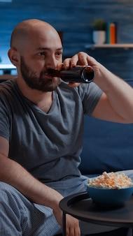 Verärgerter profi-spieler, der vor dem fernseher sitzt und fußball-videospiele verliert, während er einen drahtlosen controller hält ...