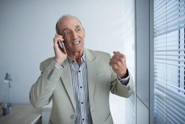 Verärgerter reifer kaukasischer geschäftsmann, der am telefon im büro spricht und faust rüttelt
