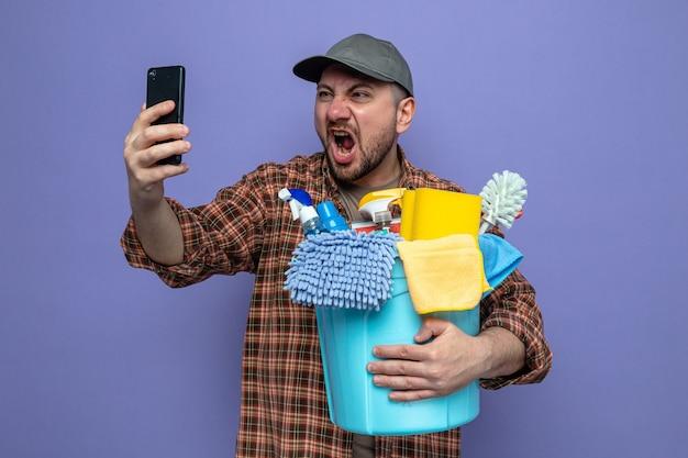 Verärgerter slawischer reinigungsmann, der reinigungsgeräte hält und jemanden anschreit, der auf das telefon schaut