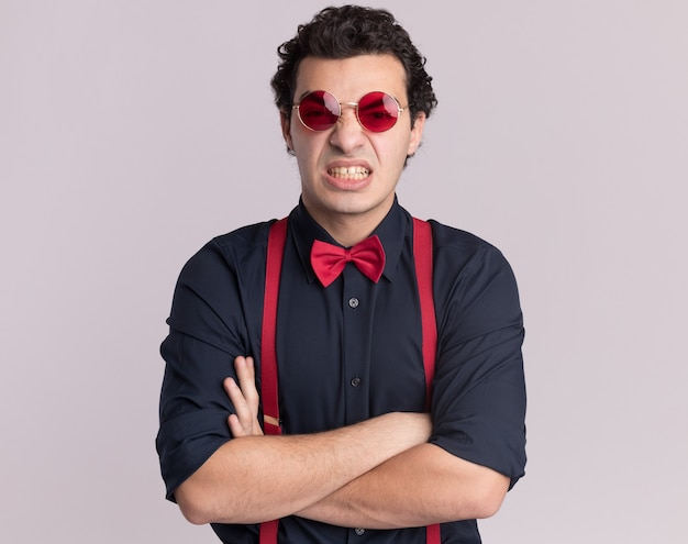 Verärgerter stilvoller mann mit fliege, die brille und hosenträger trägt, die vorne mit verschränkten armen über weißer wand stehen
