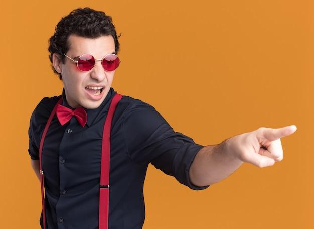 Verärgerter stilvoller mann mit fliege, die brille und hosenträger trägt, zeigt mit zeigefinger zur seite, die über orange wand steht