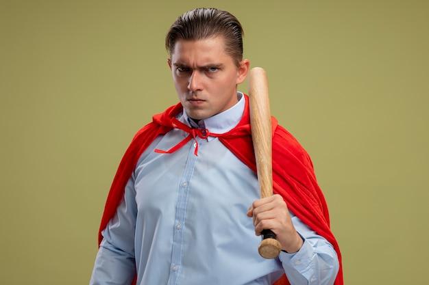 Verärgerter superheld-geschäftsmann im roten umhang, der baseballschläger hält, der kamera mit ernstem sicherem ausdruck über hellem hintergrund betrachtet