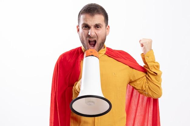 Verärgerter superheld mann mit rotem umhang hält faust und schreit in lautsprecher isoliert auf weißer wand