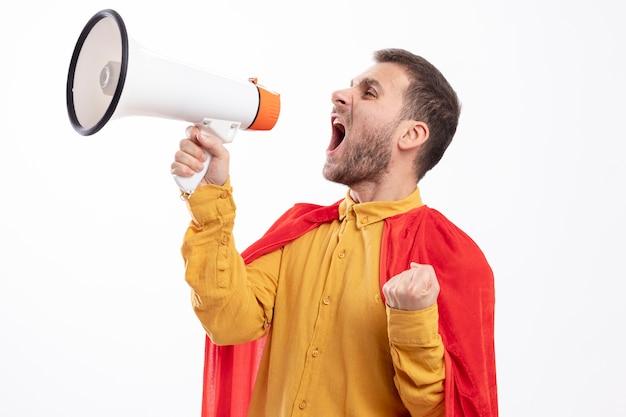 Verärgerter superheldenmann mit rotem umhang hält faust und schreit in lautsprecher, der seite betrachtet, die auf weißer wand isoliert ist