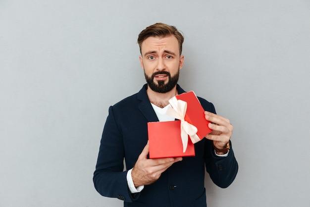 Verärgerter trauriger mann im anzug, der geschenk hält und kamera lokalisiert