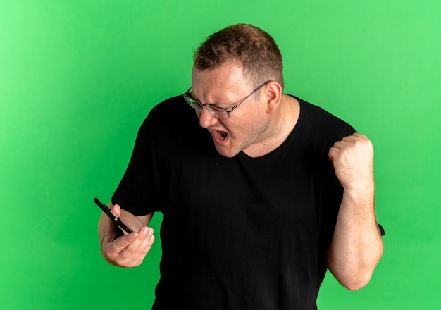 Verärgerter übergewichtiger mann in der brille, der schwarzes t-shirt trägt, das seinen smartphonebildschirm betrachtet, der die faust ballt, die mit aggressivem ausdruck über grün schreit