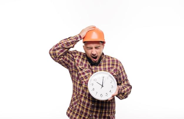 Verärgerter und geschockter baumeisterarbeiter in der schutzkonstruktion orange helm, der in der hand einen großen wecker hält, der auf weißem hintergrund lokalisiert wird. zeit zu arbeiten. bauzeit.