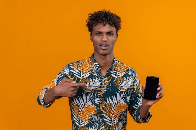Verärgerter und gestresster gutaussehender dunkelhäutiger mann mit lockigem haar, der mit zeigefinger auf leeres smartphone zeigt