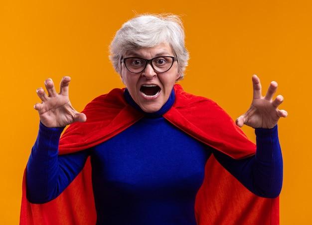 Verärgerter und irritierter senior superheldin mit brille mit rotem umhang und blick in die kamera, die krallen wie eine katze gestikuliert