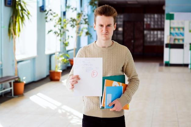 Verärgerter und verblüffter männlicher student mit schlechten prüfungsergebnissen im korridor