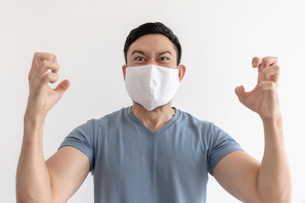 Verärgerter und verrückter asiatischer mann in gesichtsmaske auf isolierter weißer wand.