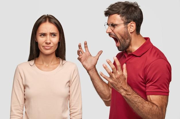 Verärgerter unrasierter kerl gestikuliert mit den händen, schreit freundin an, fühlt sich jeleaous, gestikuliert wütend