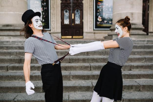 Verärgerter weiblicher pantomime, der männlichen pantomimehalter zieht