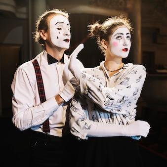 Verärgerter weiblicher pantomimen, der dem männlichen pantomimen, der hinter ihm steht, kein handzeichen zeigt
