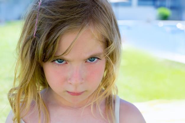 Verärgertes blondes kindermädchenportrait, das kamera schaut