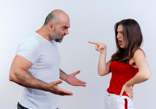 Verärgertes erwachsenes paar, das mit dem anderen mann argumentiert, der hände und frau spreizt, die hand auf taille hält und auf ihn zeigt, isoliert auf weißer wand
