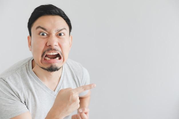 Verärgertes gesicht des mannes im grauen t-shirt mit handpunkt auf leerem raum.