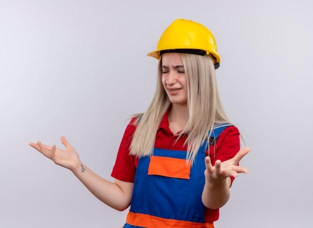 Verärgertes junges blondes ingenieur-baumeistermädchen in uniform in zahnspangen, die leere hände auf lokalisiertem weißem raum zeigen
