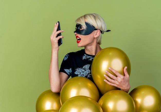 Verärgertes junges blondes partygirl, das maskerademaske trägt, die hinter luftballons steht, die einen von ihnen halten halten und betrachten handy lokalisiert auf olivgrünem hintergrund mit kopienraum