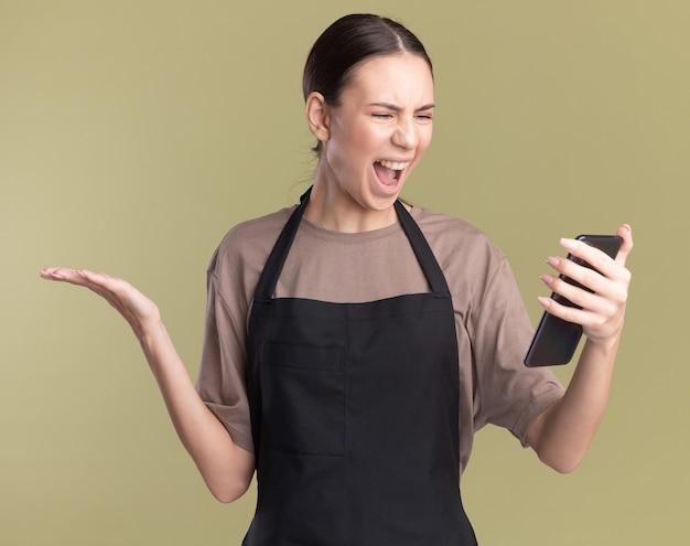 Verärgertes junges brünettes friseurmädchen in der uniform hält hand offen, die telefon auf olivgrün hält und betrachtet