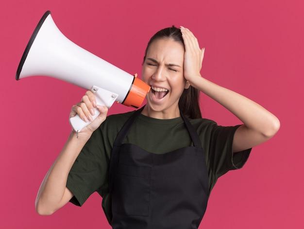 Verärgertes junges brünettes friseurmädchen in uniform legt die hand auf den kopf und schreit in den lautsprecher