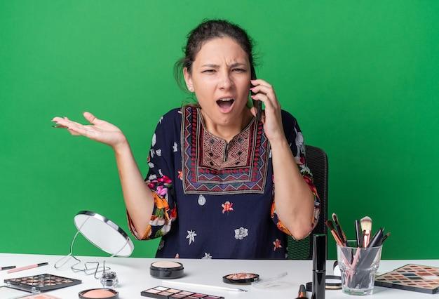 Verärgertes junges brünettes mädchen, das am tisch mit make-up-tools sitzt und jemanden am telefon anschreit, isoliert auf grüner wand mit kopierraum
